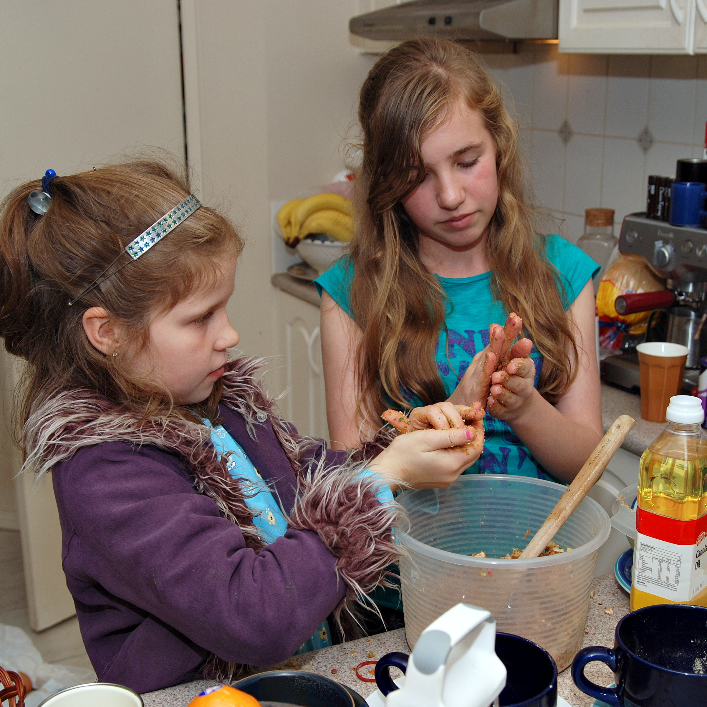 sisters using hands to prepare baking