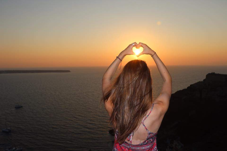 young woman shaping her hands as a heart and framing a sunset over Oia, Santorini
